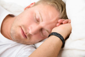 Close-up Of Young Man Sleeping Wearing Smart Wristband